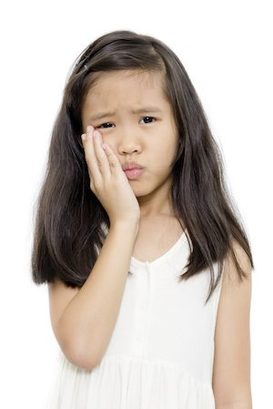 Little girl with toothache action isolated on white background needs to see an emergency dentist.