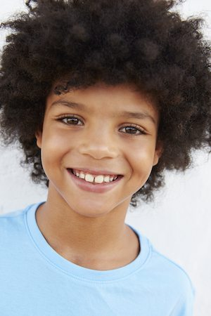 Smiling Young Boy Standing Outdoors Against White Wall
